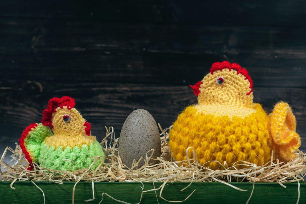 Deux poules tricotés avec un oeuf à la coquille gris entre les deux posés sur dans un nid avec de la paille.