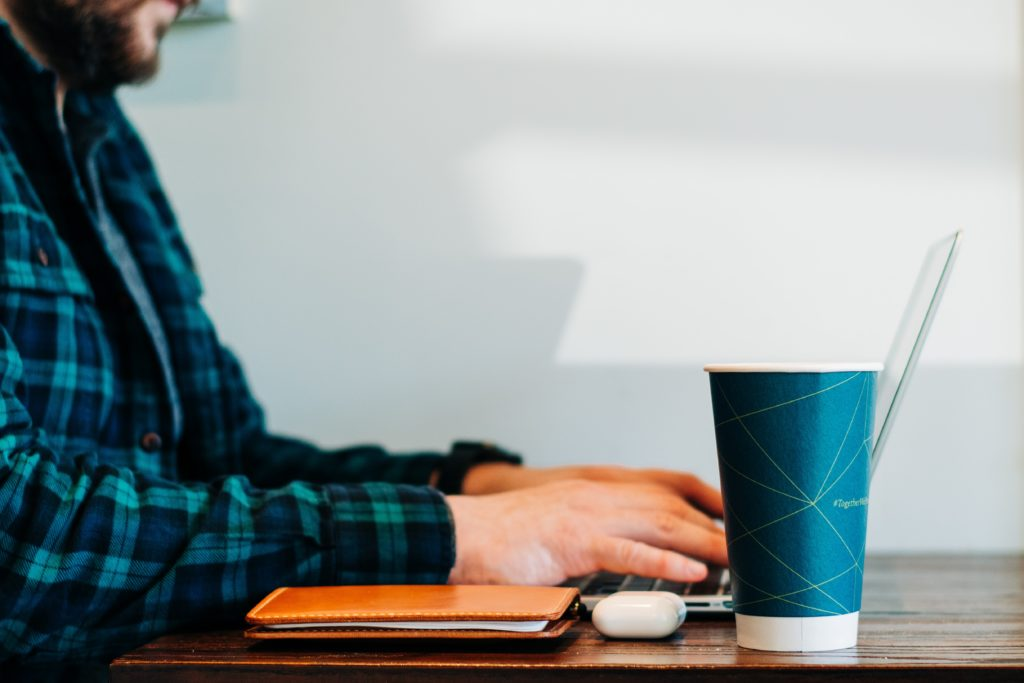 personne assise à son bureau, sur son ordinateur avec à sa droite un gobelet et un carnet