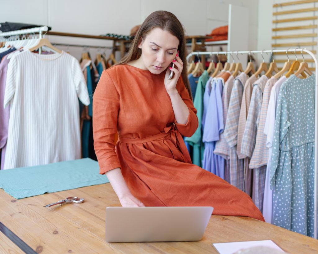 Jeune styliste travaillant dans son studio, assise sur une table dans son propre atelier, une couturière prenant une commande par téléphone et regardant son ordinateur portable, des robes à la mode suspendues à un portemanteau.