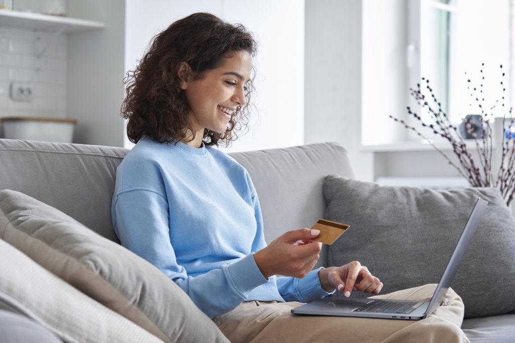 Jeune femme hispanique heureuse, consommatrice tenant une carte de crédit et un ordinateur portable, achetant en ligne à la maison. Cliente faisant des achats sur un site de marketplace, effectuant un paiement numérique en utilisant un bonus.