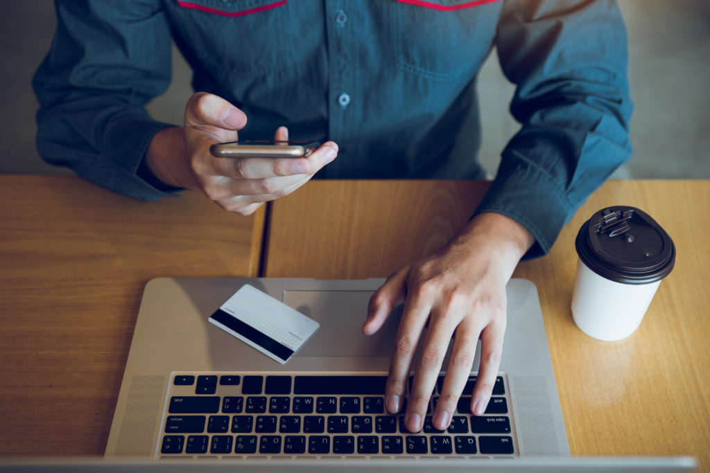 Les mains de l'homme tiennent des téléphones intelligents et utilisent des ordinateurs portables ; ils entrent sur des sites web pour acheter des produits.